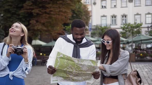 Woman Photographing Magnifincent Architecture Until Her Mixed Races Friends Looking at Tourist Map