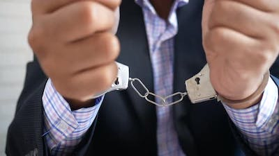 Man's Hand with Handcuff on Black Background