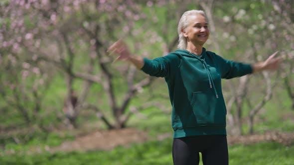 Fit Smiling Senior Sportswoman Exercising in Sunny Park on Summer Day