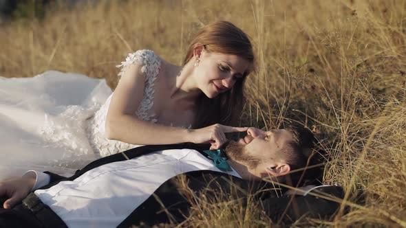 Cover Image for Newlyweds. Caucasian Groom with Bride Lie on the Grass on Mountain Slope