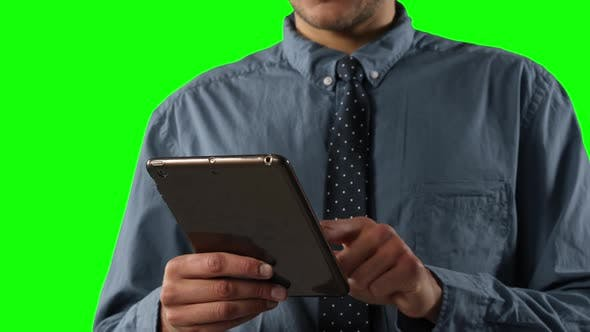 Thumbnail for Caucasian man using a digital tablet on green background