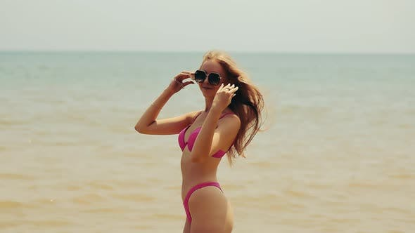 Happy Young Woman in a Bathing Suit Having Fun Dancing and Spinning Around