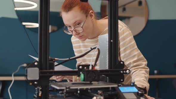Young Woman Watching 3D Printer Working