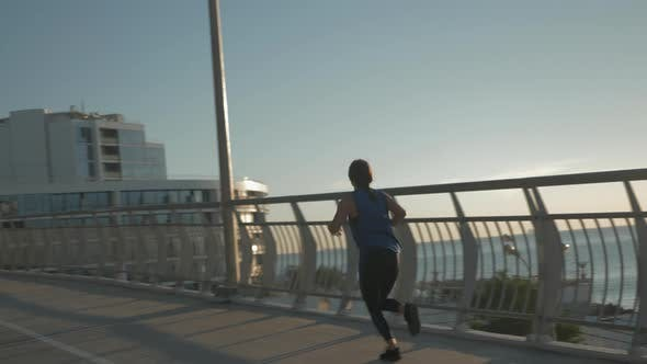 Thumbnail for Happy attractive young woman in blue sportswear is running on bridge in the morning at sunrise.