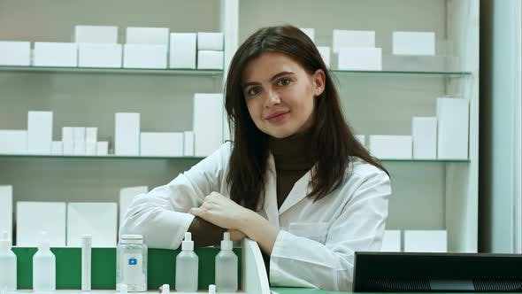 Thumbnail for Smiling Happy Confident Young Woman Pharmacist Leaning on a Desk in the Pharmacy Giving the Camera a