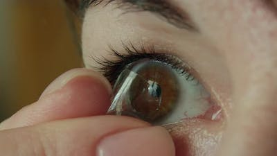 Woman with brown eyes removes a contact lens on her eye with her fingers, close-up