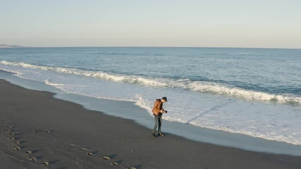 Aerial view of a photographer by the ocean
