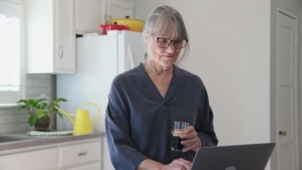 Thumbnail for Seniorin mit Laptop-Computer in der Küche beim Trinken von Eiskaffee