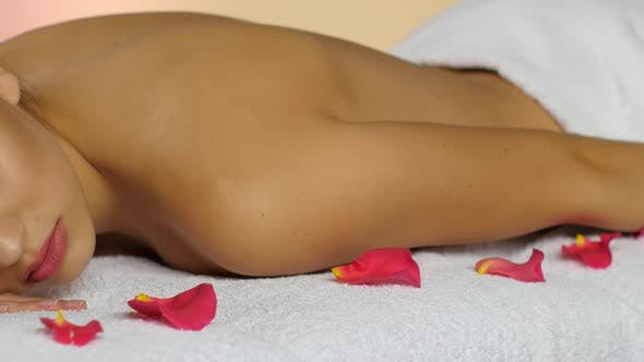 Thumbnail for Girl on Towels with Rose Petals Sleeps After Spa Treatments