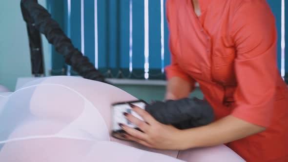 Femme en uniforme fait le massage à rouleau sous vide de la cuisse dame