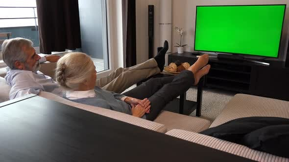 Thumbnail for An Elderly Couple Sits in A Living Room in An Apartment and Watches TV with A Green Screen