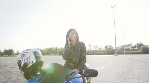 Thumbnail for Young Biker Girl with Dark Hair in a Leather Jacket and Sunglasses Sits