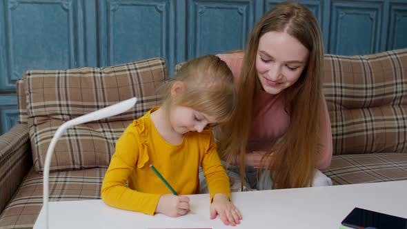Lovely Mother Babysitter Teacher Helping Kid Daughter with Homework Learning Drawing at Home
