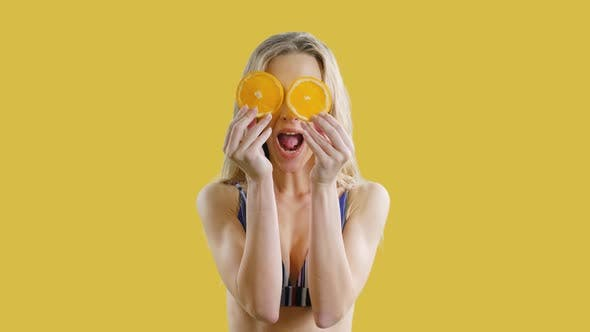 Young Beautiful Girl Is Smiling with Oranges in Hands on an Yellow Background. Happy Healthy Skinny