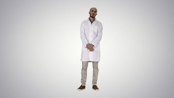 Thumbnail for Standing Young Serious Arab Doctor on Gradient Background.