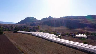 Greenhouses on Farm Fields in Mountains