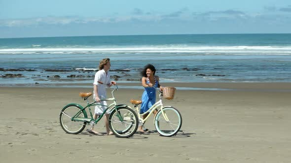 Cover Image for Couple walk with bicycles along coastline