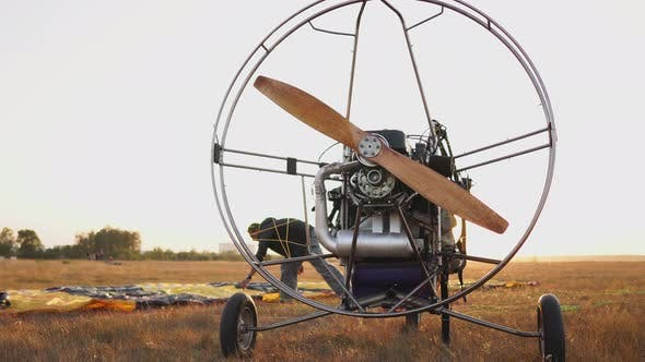 Thumbnail for The Motor Paraglider Stands in the Field at Sunset with a Wooden Propeller, and the Pilot Lays Out