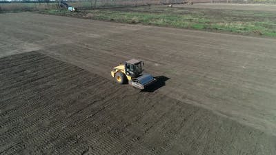 High Angle View of a Compactor Driving in the Field Leveling the Ground