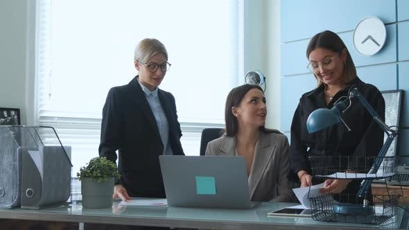 Three Young girls are talking about business in their office and checking documents