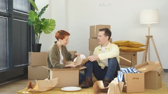 Caucasian Family Moving to New Apartment Surrounded with Plenty of Cardboard Boxes