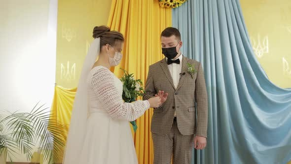 Cover Image for Newlyweds. Caucasian Groom with Bride Exchanging Rings on Wedding Ceremony. Coronavirus Covid-19