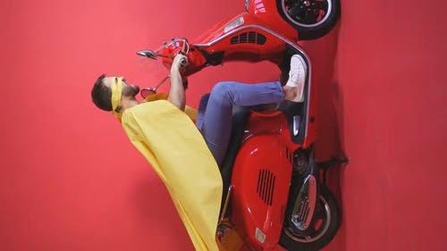Crazy Man Driving a Moped Scooter in Cape and Mask Party in the Role of a Super Hero, Isolated