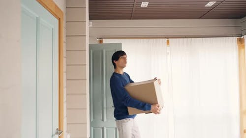 Happy Couple Bringing Boxes with Personal Things After Relocation To New House