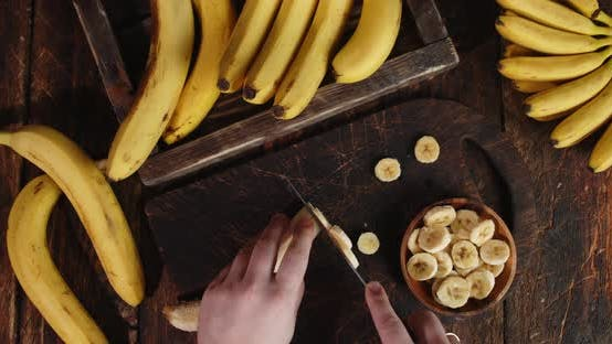 Male Hands Slicing the Banana on a Cutting Board.