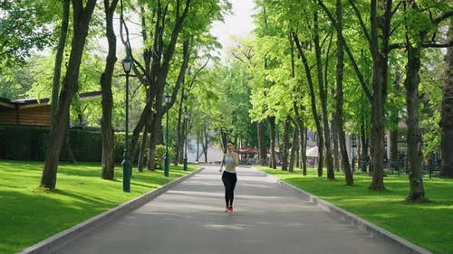 Woman with Curvy Forms Jogging in Park