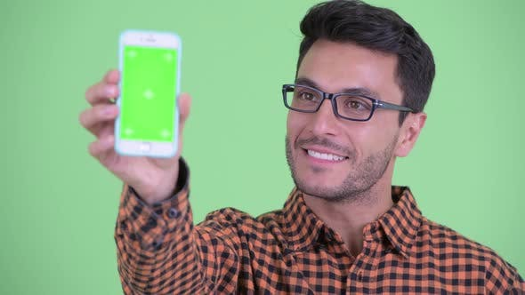 Face of Happy Young Hispanic Hipster Man Showing Phone