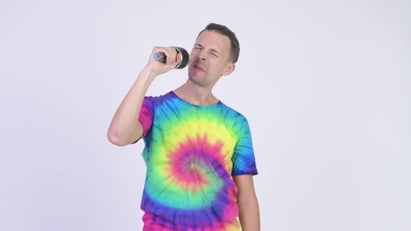 Cover Image for Studio Shot of Man with Tie-dye Shirt Singing with Microphone