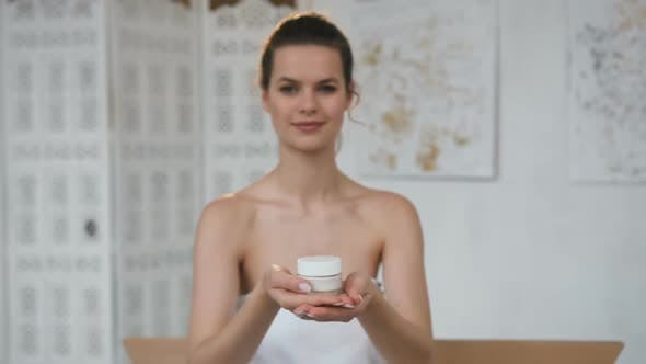 Thumbnail for Handsome Cute Woman Stretching Out Jar with Cream to the Camera