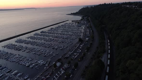 Thumbnail for Aerial Of Boats Docked At Ocean Marina With Train And Cars Passing