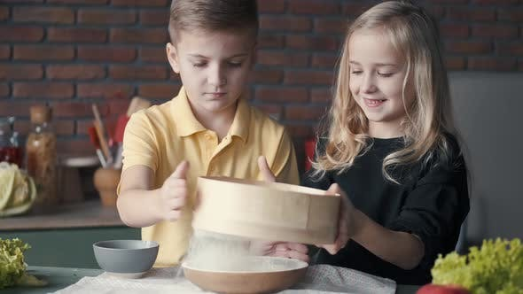 Thumbnail for Kids Are Sieveing Flour Into a Bowl Together in a Modern Kitchen