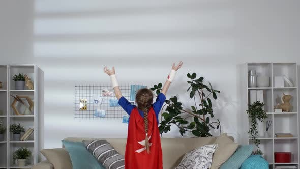 Thumbnail for Little Girl in Superhero Costume Holding Arms Raised in Kids Room