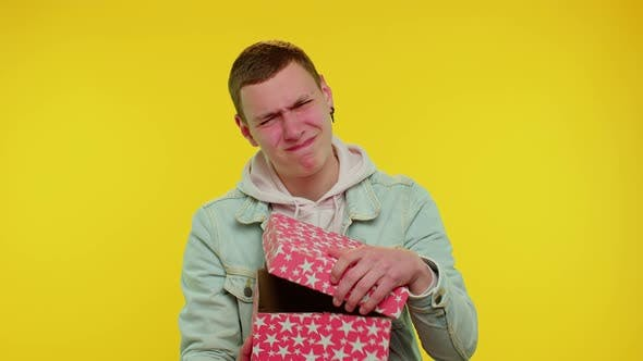 Young Man Unwrapping Birthday Gift and Expressing Disappointment Dislike Bad Present Dissatisfied