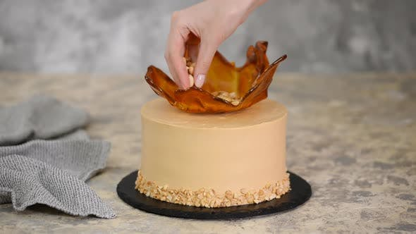 Thumbnail for Pastry chef decorating the caramel cake with a peanuts.