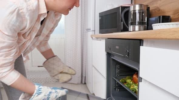 Frau zieht Fertigfutter aus dem Ofenhähnchen mit Gemüse