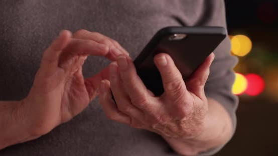 Thumbnail for Close-up of mature woman using smartphone to read messages on bokeh background