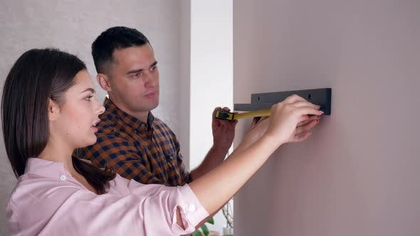 Married Couple Hanging Shelf on Wall with Tape Measure in Arms During Repairs in Accommodation
