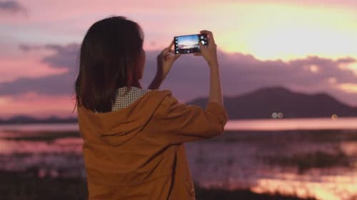 Asian lady with backpack using phone for take a picture in camping on beach at night.