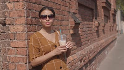 Woman Drinking Iced Coffee Outdoors