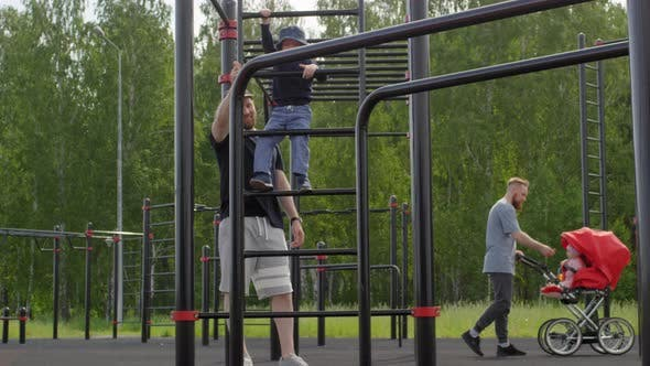 Cover Image for Two Caucasian Dads Walking with Kids at Outdoor Gym in Park