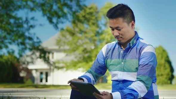 Thumbnail for Asian Man Working with Tablet
