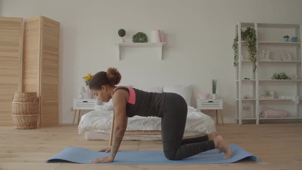 Graceful Fitness Woman Doing Cat Cow Pose Indoors