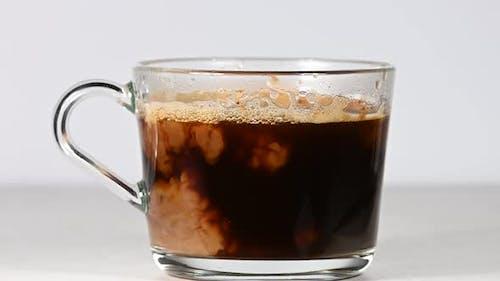 Nahaufnahme Gießen Milch in Glas Tasse schwarzen Kaffee