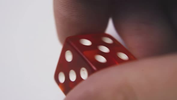 Person Shows Red Plastic Dice with Symbol Five Macro