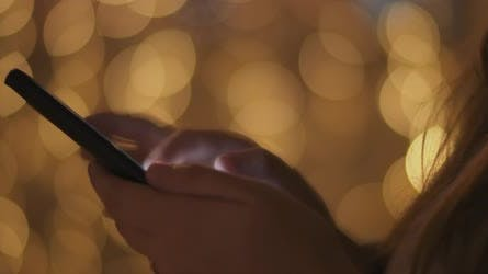 Close up of a young woman's hands scrolling over social media on her phone