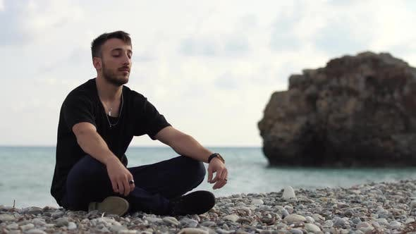 Cover Image for Young Man with Closed Eyes Sitting and Relaxing in Yoga Style Near Amazing Sea Side View
